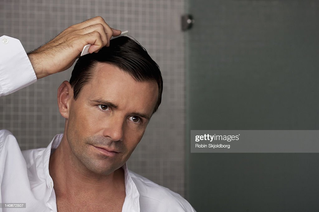 Man combing his hair in bathroom : Stock Photo