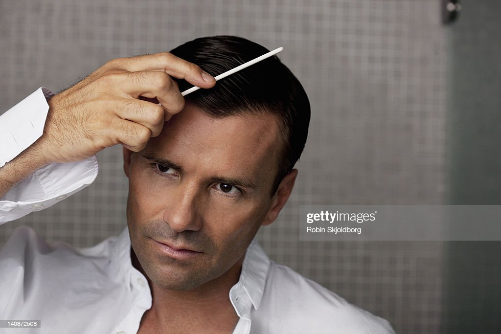 Man combing his hair in bathroom : Stock Photo