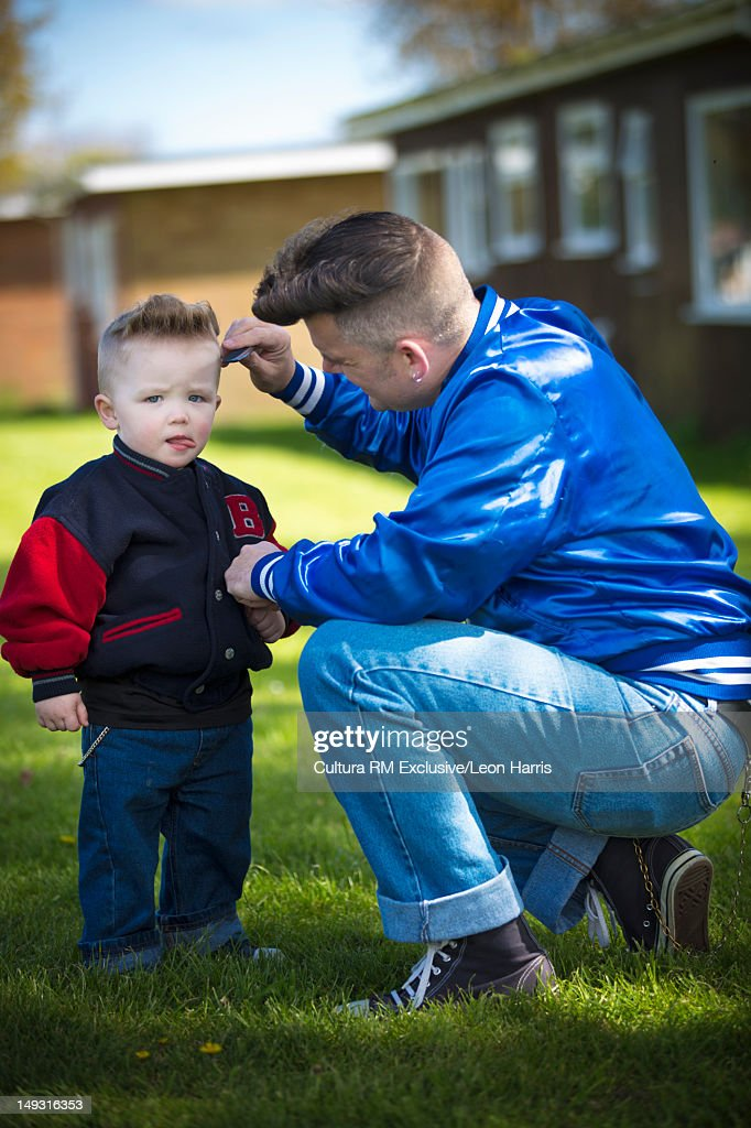 Man combing sons hair : Stock Photo