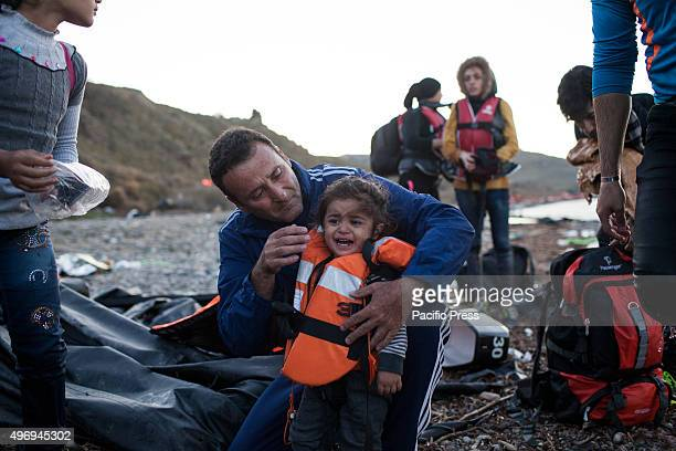 A man comforts a child as they reached the shores of the Greek island of Lesbos after crossing the Aegean Sea from Turkey through dinghy