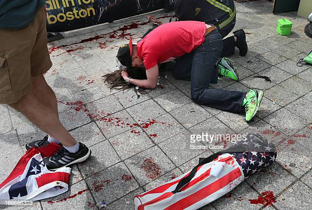 A man comforts a victim on the sidewalk at the scene of the first explosion near the finish line of the 117th Boston Marathon