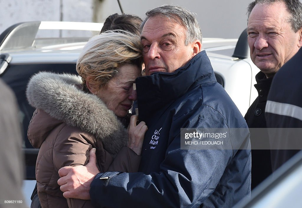 A man comforts a woman in tears at the Rochefort rescue center on February 11, 2016 after at least six children were killed when a school bus crashed into a truck, police said, a day after another road accident involving a school bus left two youngsters dead. The head-on smash with a lorry carrying rubble happened at around 7:15 am (0615 GMT) in Rochefort in the Charente-Maritime region. / AFP / MEHDI FEDOUACH