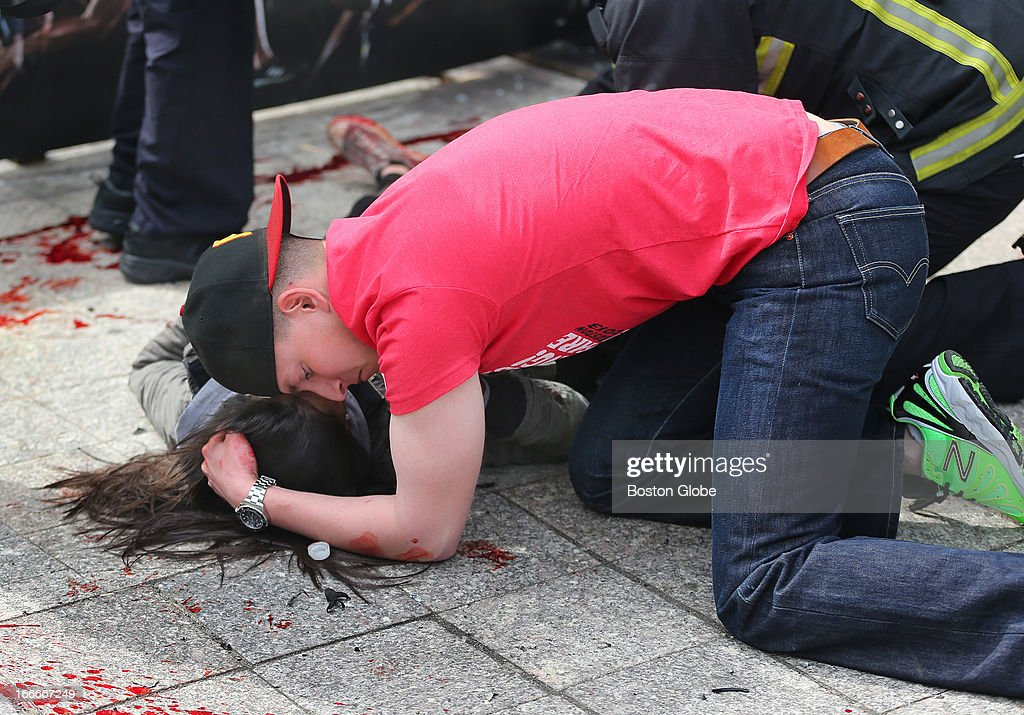 A man comforts an injured woman on the sidewalk at the scene of the first explosion on Boylston Street near the finish line of the Boston Marathon.