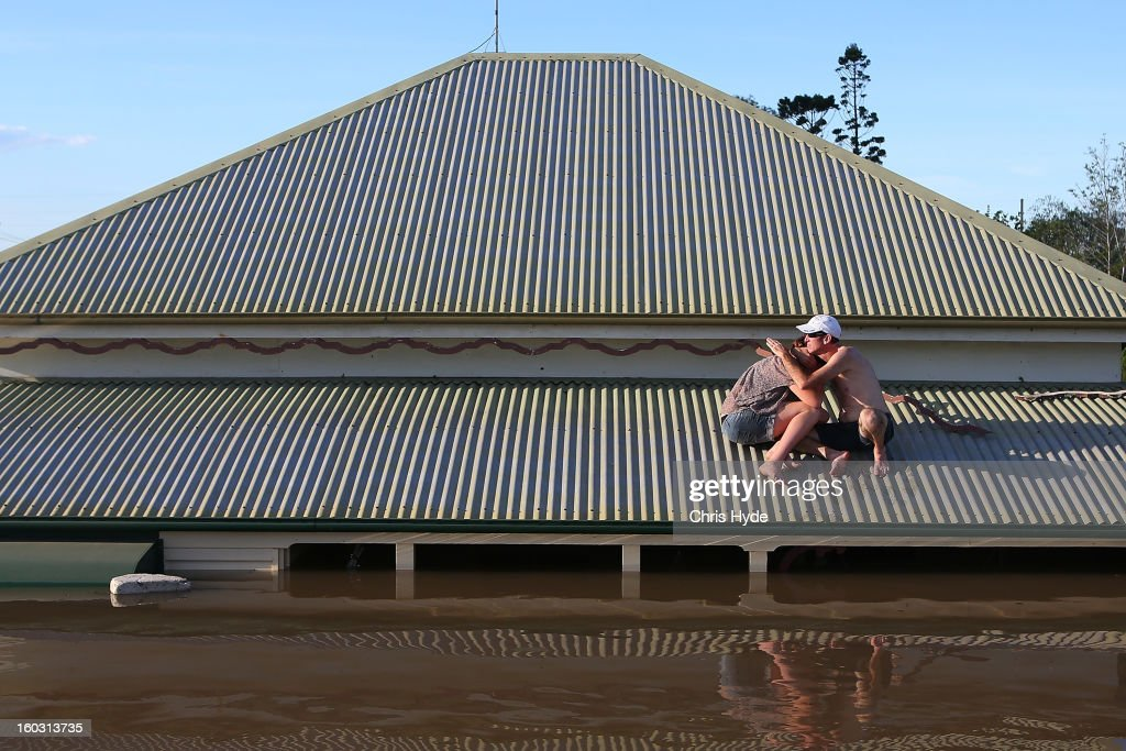 A man comforts his daughter on their roof as they inspect damage to their neighbourhood as parts of southern Queensland experiences record flooding in the wake of Tropical Cyclone Oswald on January 29, 2013 in Bundaberg, Australia.Four deaths have been confirmed and thousands have been evacuated in Bundaberg as the city faces it's worst flood disaster in history. Rescue and evacuation missions continue today as emergency services prepare to move patients from Bundaberg Hospital to Brisbane amid fears the hospital could lose power.