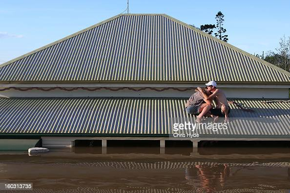 A man comforts his daughter on their roof as they inspect damage to their neighbourhood as parts of southern Queensland experiences record flooding...