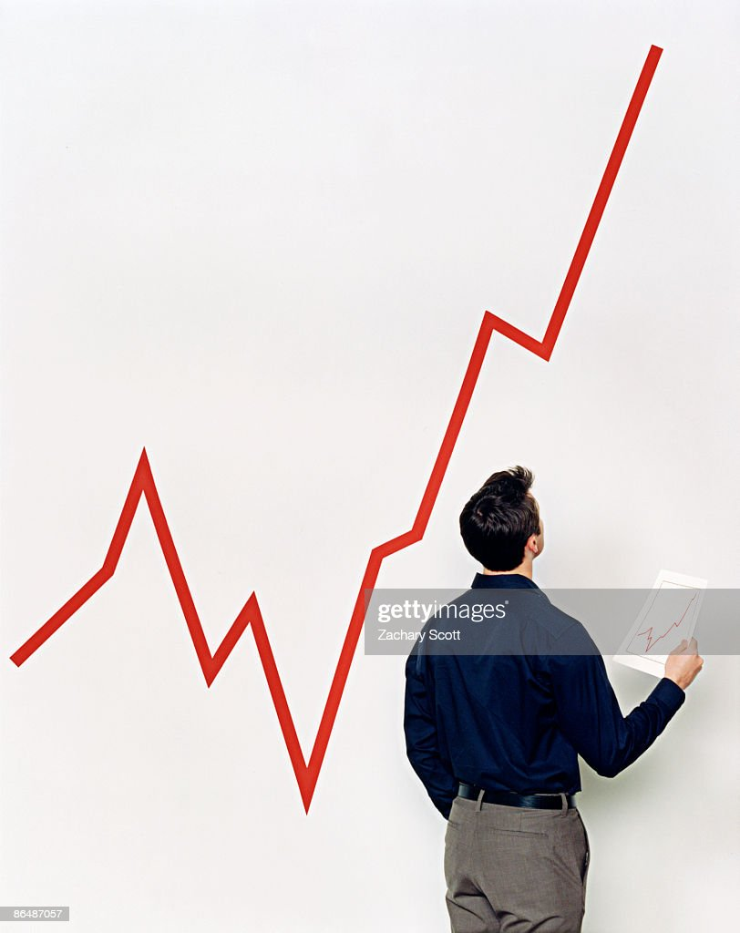 man compares small growth chart to large chart : Stock Photo