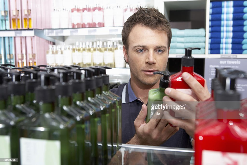 man comparing two cream bottles : Stock Photo