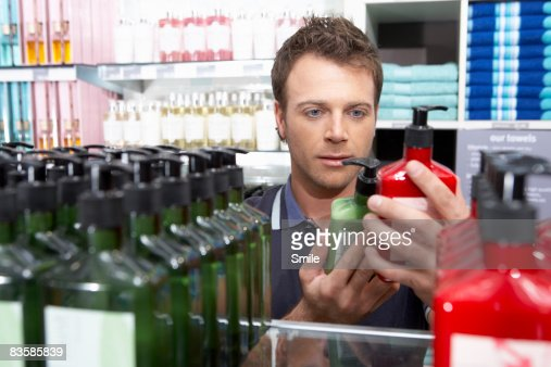 man comparing two cream bottles : Stock Photo