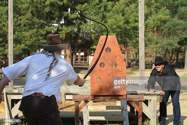 A man competes with a whip in the 1st European Championship in throwing knives at a target tomahawk throwing shooting a revolver and whipping in...
