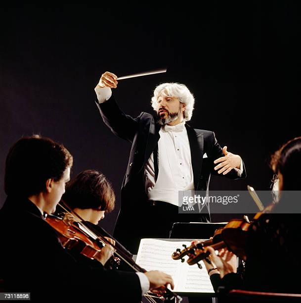 Man conducting orchestra, view from violin section