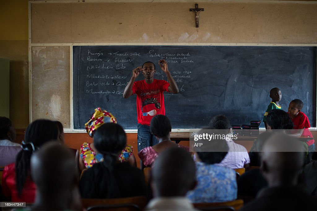 A man conducts a choir in a classroom at St. Theresa's church in the Eastleigh neighbourhood of Nairobi, Kenya, on March 10, 2013. Kenyans called Sunday for reconciliation between the winning and losing camps in the presidential poll, a day after Uhuru Kenyatta, who faces an international trial for crimes against humanity, was declared the winner but his chief rival refused to concede. AFP PHOTO/PHIL MOORE