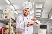 Man confectioner  with a cake in his hands in the pastry bakery.