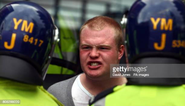 A man confronts police as he boards a bus where English Defence League supporters have been put on by police following their demonstration in...