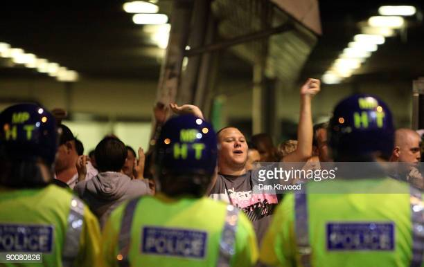 A man confronts riot police outside the West Ham football ground on August 25 2009 in London England Violence broke out between West Ham and Millwall...