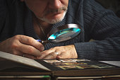 Man considers album of  stamps trough the magnifying glass horizontal