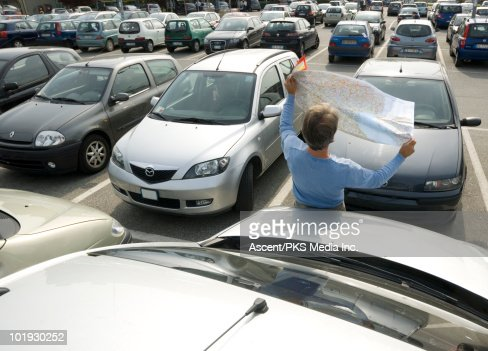 Man consults road map in full parking lot : Stock Photo