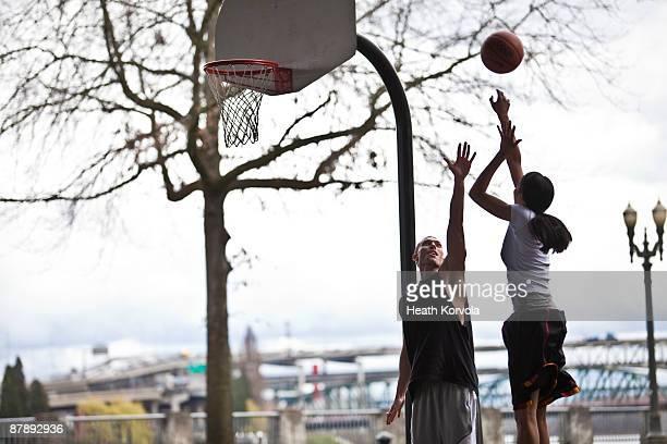 A man contests a basketball shot.