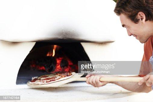A man cooking a woodfire pizza. : Bildbanksbilder