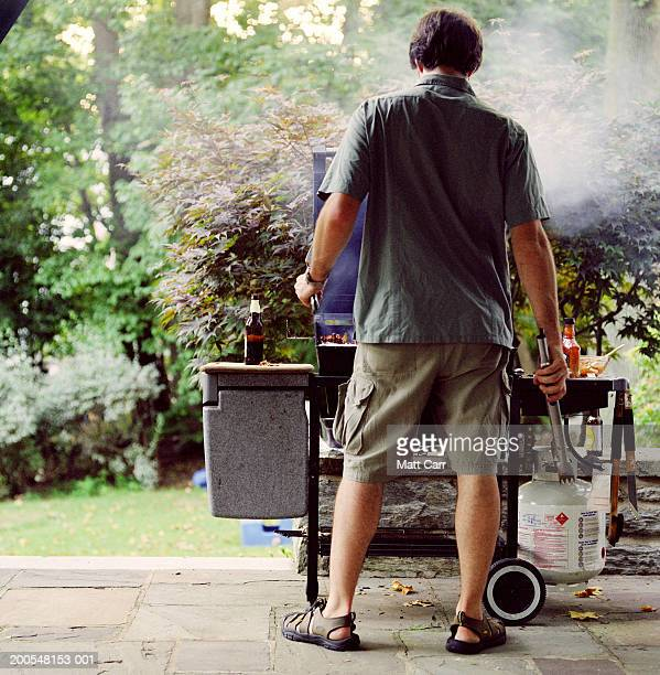 Man cooking at grill, rear view