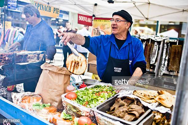 Man cooking food on outdoors market, New York
