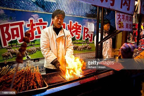 Man cooking lamb skewers at Uighur food stall on Wangfujing Snack Street.