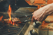 Man cooking meat steaks on professional grill outdoors. Male hand with tongs flipping beefsteaks on open fire