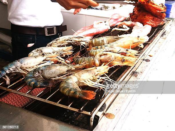 Man Cooking Prawn On Barbecue Grill