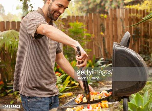 Man cooking vegetable skewers on barbecue