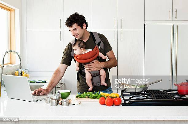 Man cooking while holding baby