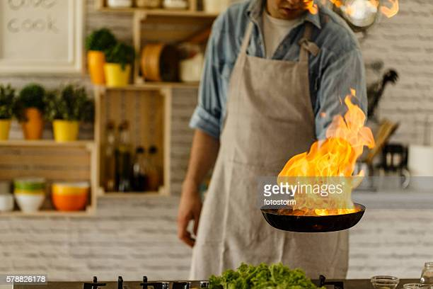 Man cooking with fire in kitchen
