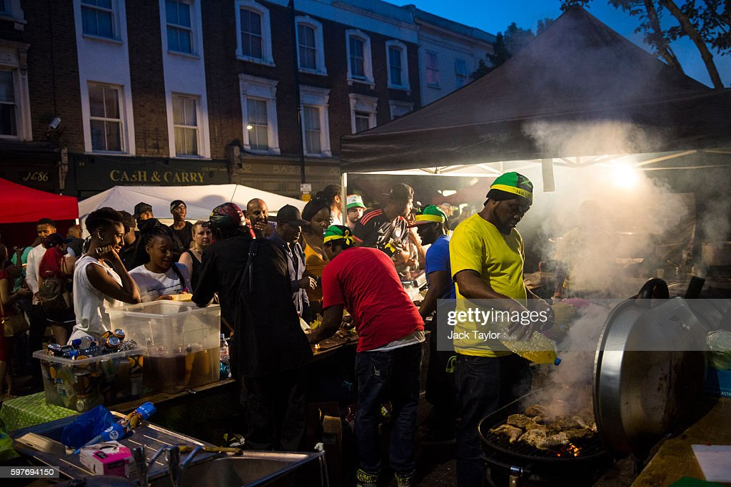 A man cooks chicken as customers queue for food at the Notting Hill Carnival on August 29 2016 in London England The Notting Hill Carnival which has...