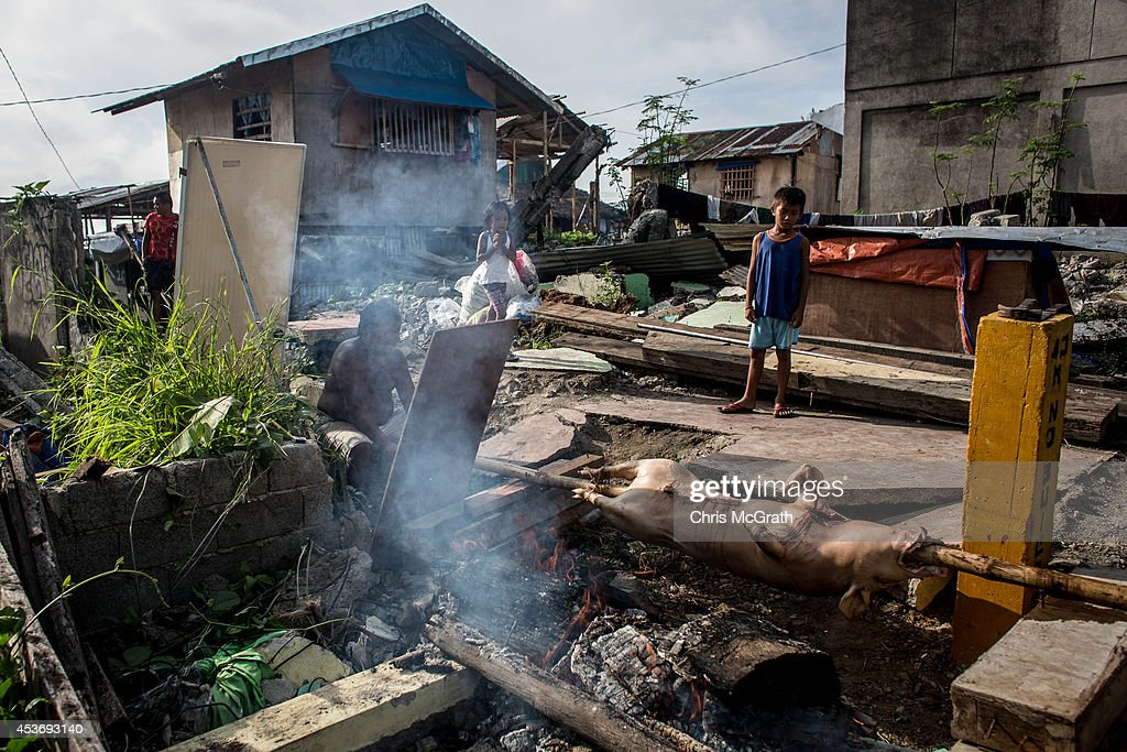A man cooks Lechon (roasted pork) for Fiesta lunch in a destroyed area of Magallanes district on August 16, 2014 in Tacloban, Leyte, Philippines. Fiesta is an annual celebration held by each town. The day generally starts with an early morning parade, before families gather at home for a large lunch often sharing the Philippine national food Lechon. Residents of Tacloban city and the surrounding areas continue to focus on rebuilding their lives nine months after Typhoon Haiyan struck the coast on November 8, 2013, leaving more than 6000 dead and many more homeless. With many businesses and government operations back up and running and with the recent start of the years typhoon season, permanent housing continues to be the main focus with many families still living in temporary accommodation. As well as continuing recovery efforts Leyte is preparing for the arrival of Pope Francis, who will visit the region from January 15- 19. on August 16, 2014 in Tacloban, Leyte, Philippines.