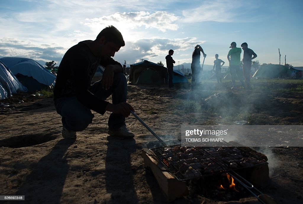 A man cooks meat at a makeshift camp for migrants and refugees at the Greek-Macedonian border near the village of Idomeni on April 30, 2016. Some 54,000 people, many of them fleeing the war in Syria, have been stranded on Greek territory since the closure of the migrant route through the Balkans in February. / AFP / TOBIAS