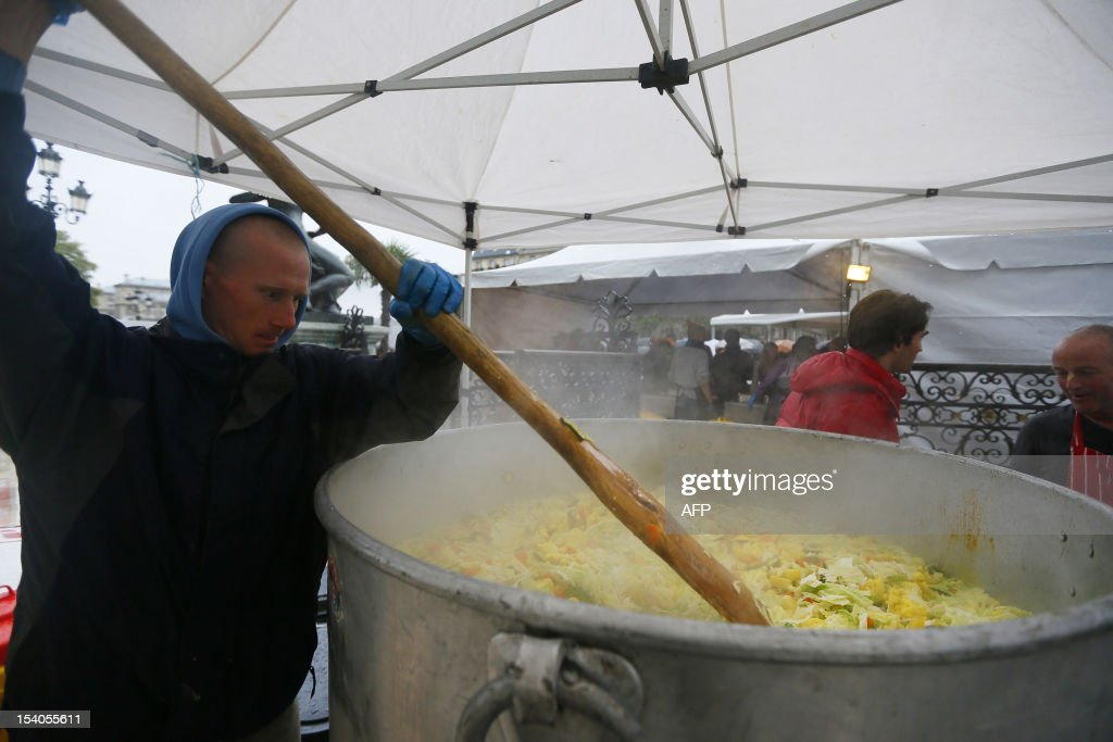 A man cooks vegetables during an event to raise awareness of the food waste on October 13, 2012 at the Place de l'Hotel de Ville in Paris. Five thousand people were invited to enjoy a giant curry prepared using 800 kg of twisted carrots and uncalibrated vegetables that supermarkets refuse to buy from producers and which usually end in disposal. 'While one billion people suffer from malnutrition in the world, a third of the food produced ends up in the trash! I am green since I was 4 years' said Stuart.