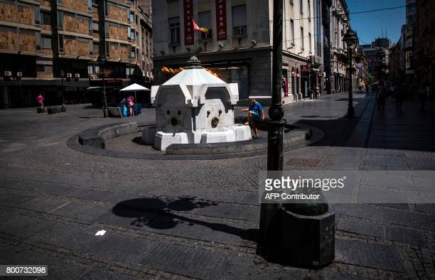 A man cools off at a fountain in the Serbian capital Belgrade on June 25 2017 as a heat wave sweeps the country with temperatures reaching 40 degrees...