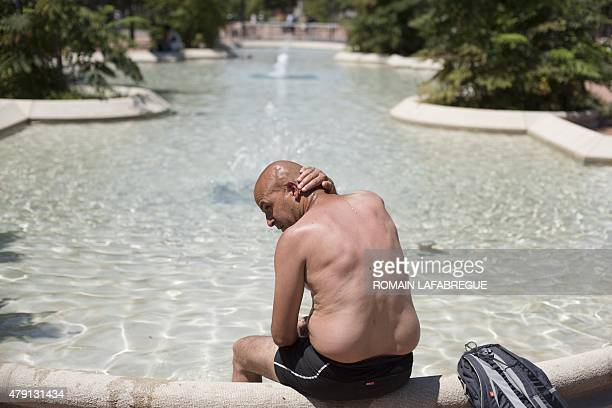 A man cools off in a public fountain on July 1 in Lyon central eastern France as a blistering heatwave sweeps through Europe with temperatures...