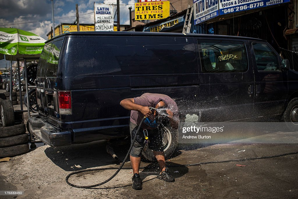 A man cools off with a hose on August 2, 2013 in the Willet's Point neighborhood of the Queens borough of New York City. The neighborhood has been in a battle with the city of New York for years, which plans to demolish the neighborhood and invest $3 billion for a mall, apartments and more parking for nearby Citi Field. Members of the neighborhood argue that over two hundred small businesses are established in the neighborhood and should not be evicted.