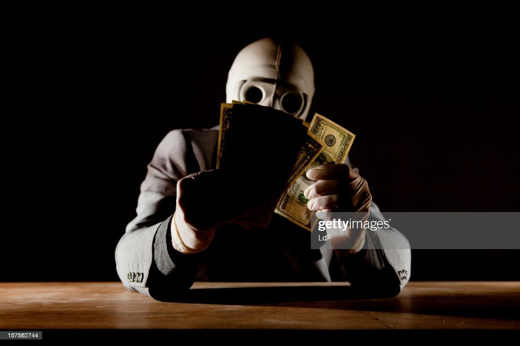 Man counting dollars wearing a gas mask : Stock Photo