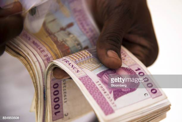 A man counts 10000 denomination Central African franc banknotes in this arranged photograph in N'Djamena Chad on Wednesday Aug 16 2017 African...