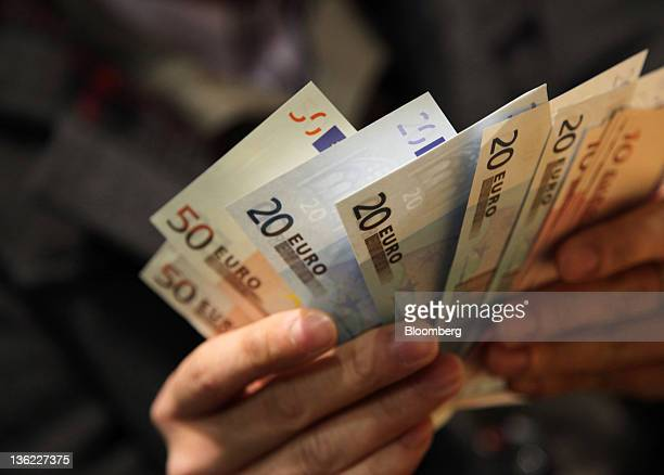 A man counts euro notes in this arranged photograph in Tokyo Japan on Thursday Dec 29 2011 The euro weakened to a decade low against the yen before...