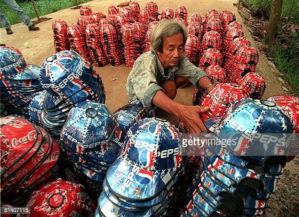 A man counts hats made of used Coke and Pepsi cans before delivering them to sell in Ho Chi Minh City on 21 September 1999 Some family workshops in...