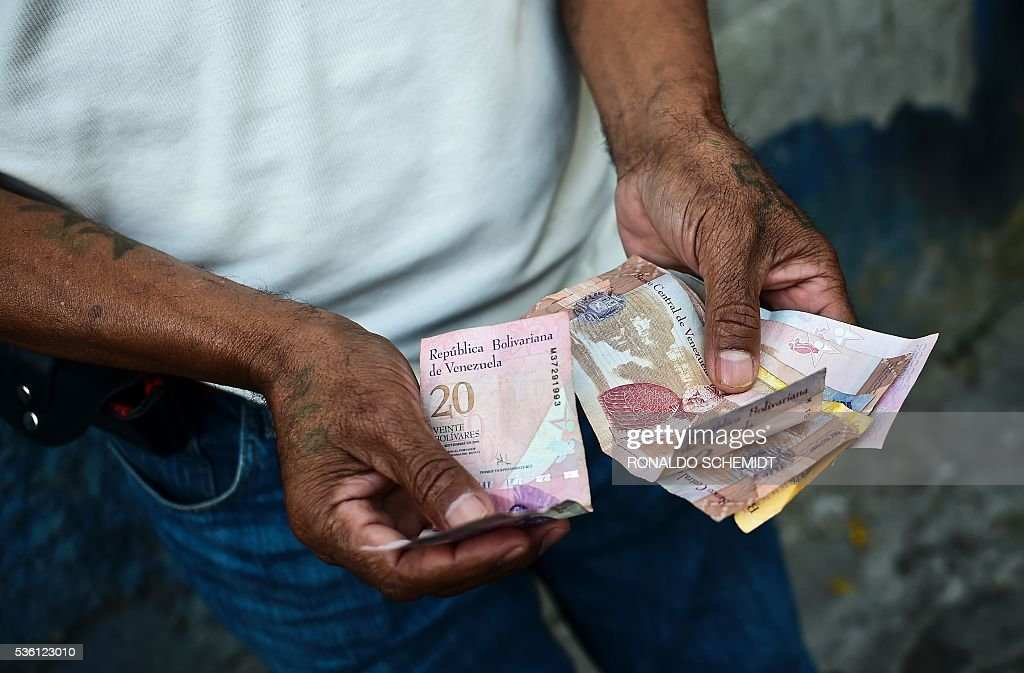 A man counts money as he queues to buy basic food and household items outside a supermarket in the poor neighbourhood of Lidice, in Caracas, Venezuela, on May 31, 2016. The oil-dependent nation faces severe food and medicine shortages, school closures and a cut in electricity production which has led to a dramatically shortened workweek for public sector employees. / AFP / RONALDO