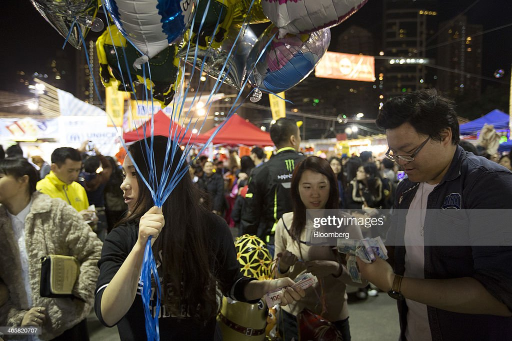 A man counts money to pay for balloons at the Lunar New Year fair at Victoria Park in Hong Kong, China, on Wednesday, Jan. 29, 2014. The citys financial markets will close early on Jan. 30 for the Chinese New Year holidays and resume trading on Feb. 4, while those in the mainland will be shut from tomorrow through Feb. 6. Photographer: Brent Lewin/Bloomberg via Getty Images
