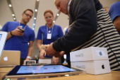A man counts out cash while purchasing two new Apple iPhone 5S smartphones at the Berlin Apple Store on the first day of sales on September 20 2013...