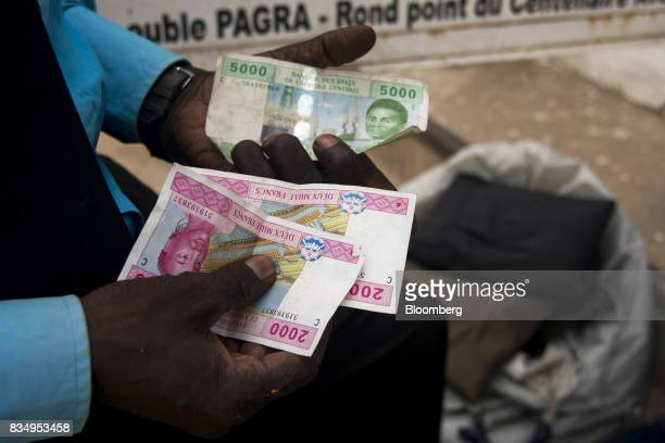 A man counts out Central African franc banknotes on a street in N'Djamena Chad on Wednesday Aug 16 2017 African Development Bank and nations signed...