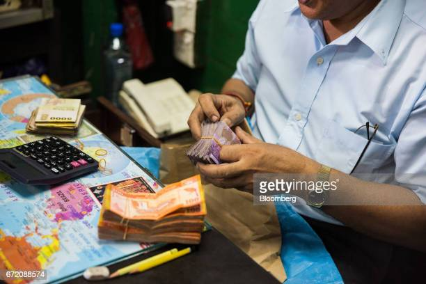 A man counts Sri Lankan rupee banknotes at an edible oil wholesale store in the Pettah neighborhood of Colombo Sri Lanka on Thursday April 20 2017...