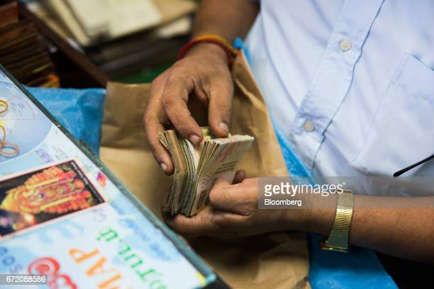 A man counts Sri Lankan rupee banknotes at wholesale store selling edible oil in the Pettah neighborhood of Colombo Sri Lanka on Thursday April 20...