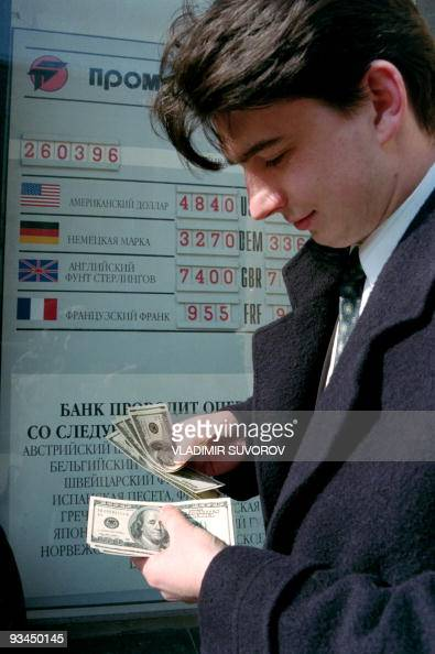 A man counts the new US$ 100 notes after changing the old ones at the exchange office on March 27 1996 Russia is the biggest holder of US currency...