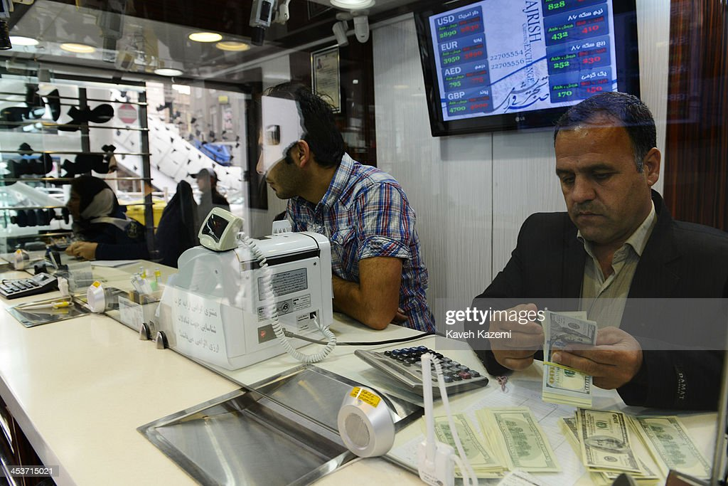 A man counts US Dollar banknotes in an official exchange house when the market prices dropped slightly after an agreement in Geneva of 5+1 group on November 25, 2013 in Tajrish square north Tehran, Iran.