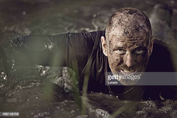 man covered by mud getting out of the water